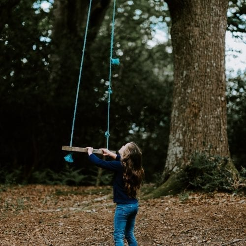 girl holding brown swing under the tree