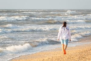 woman in white long sleeve shirt and white shorts standing on seashore during daytime