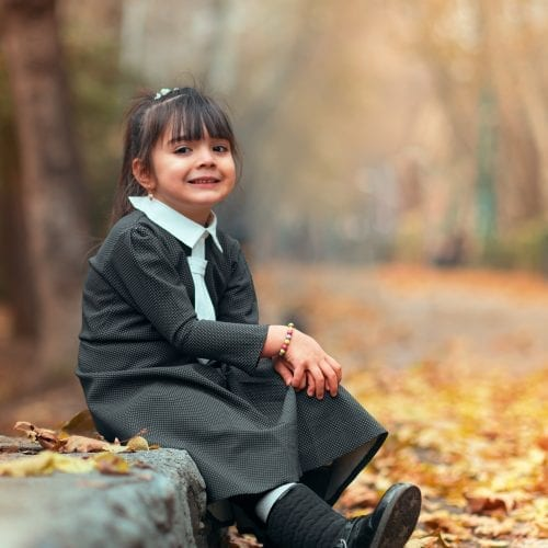 smiling girl sitting beside road