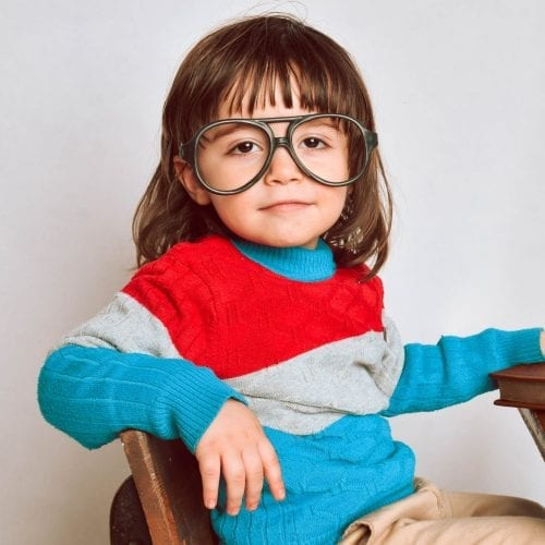 girl in red framed eyeglasses and gray sweater sitting on brown wooden chair