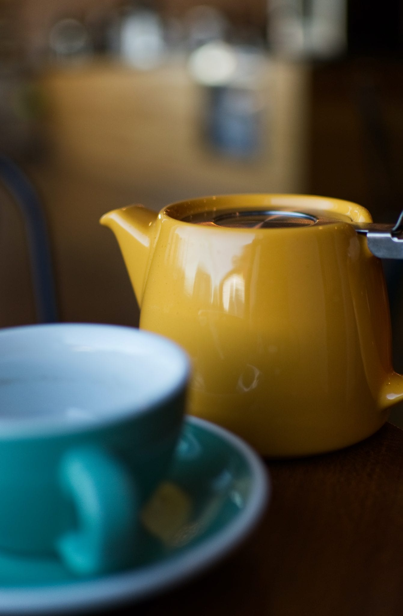 shallow focus photography of yellow ceramic teapot