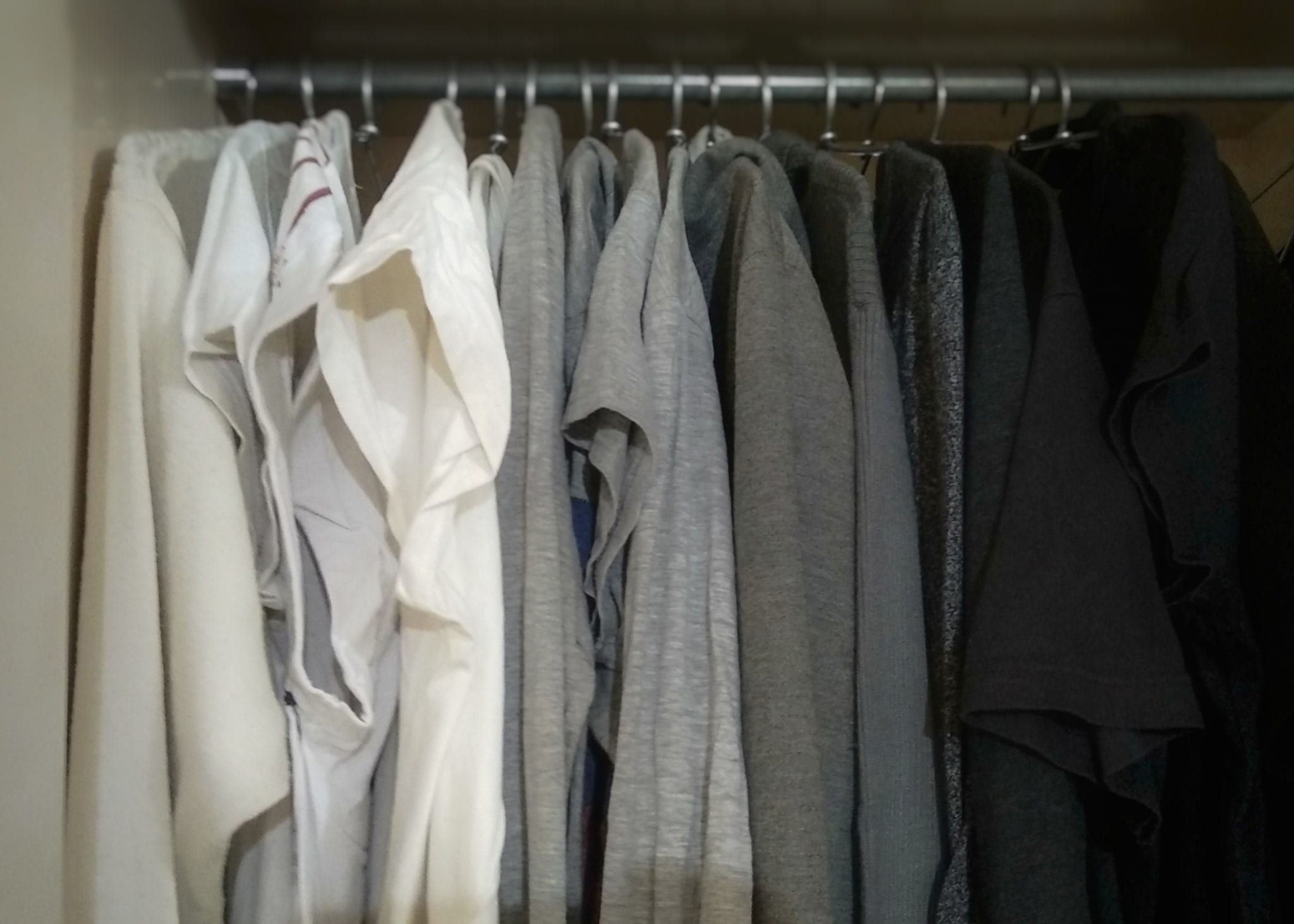 white and black clothes hanging on rack