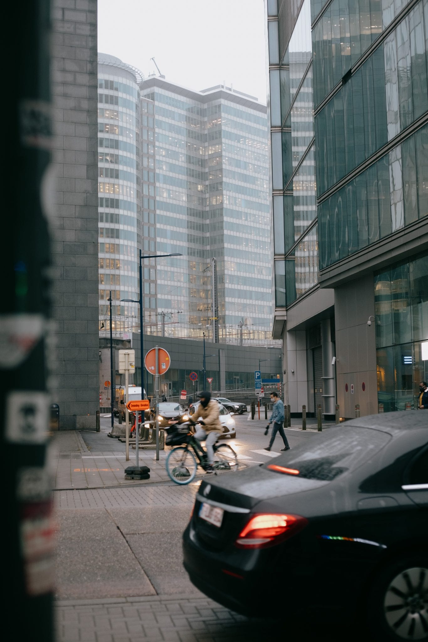 people riding motorcycle on road near high rise buildings during daytime