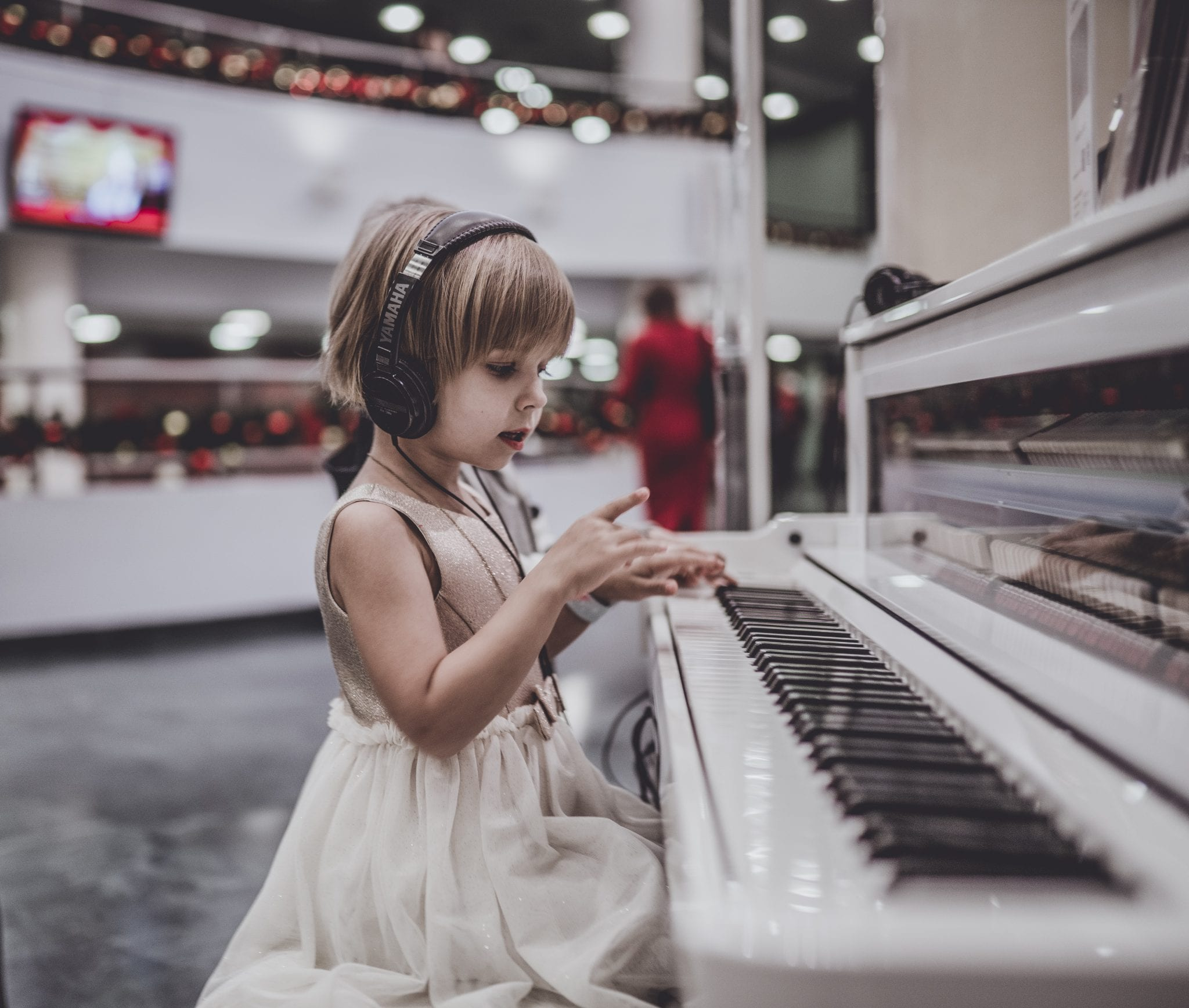 girl wearing headphones sitting in front of white piano