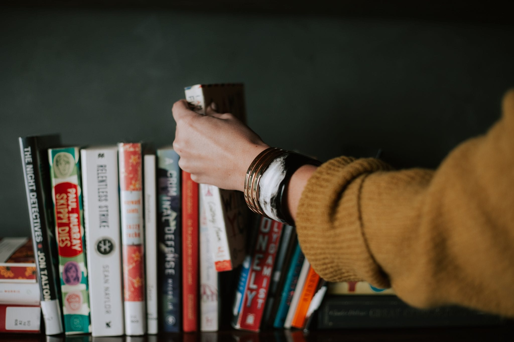 person picking white and red book on bookshelf