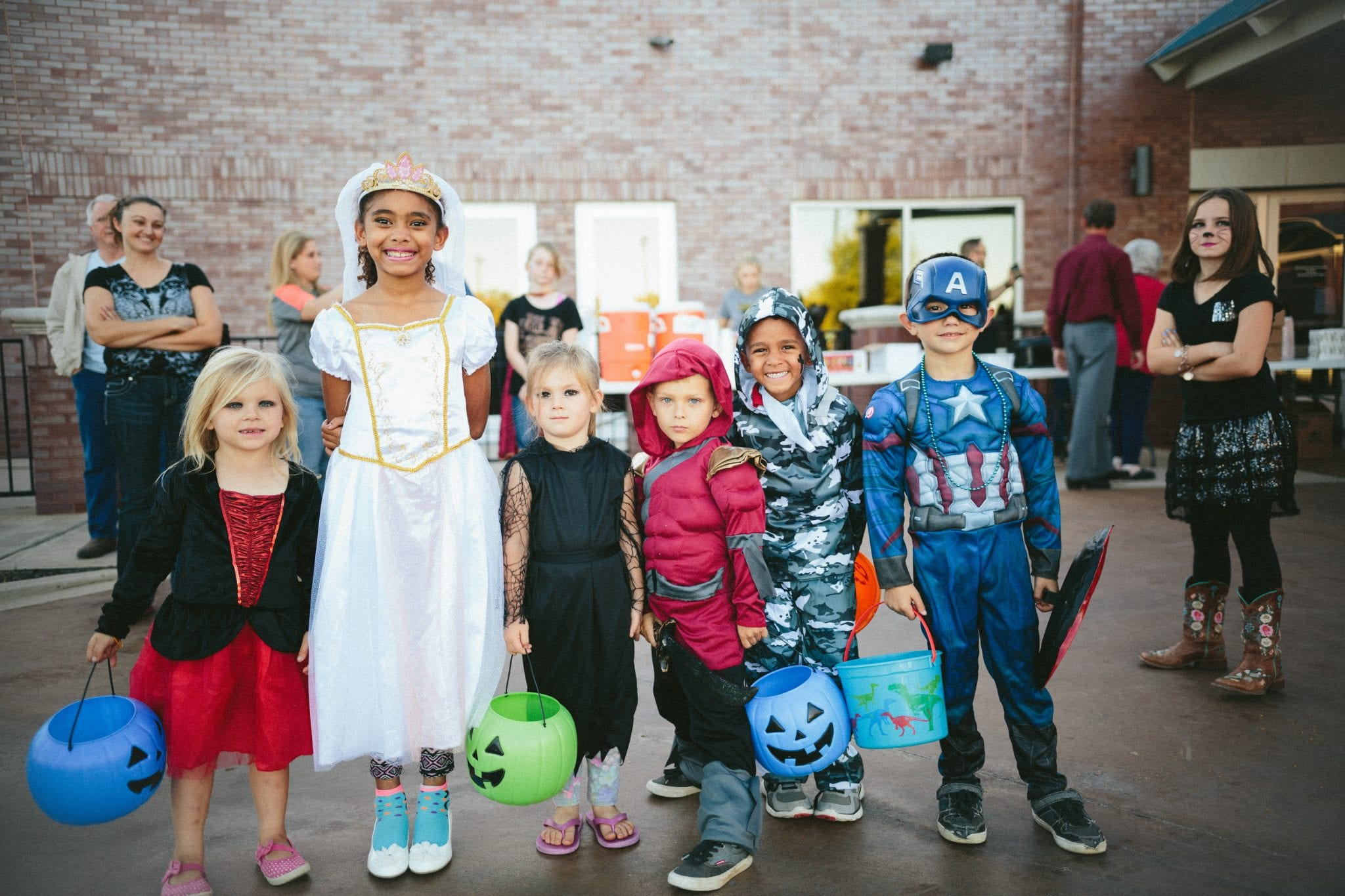 children standing while holding Jack 'o lantern and wearing costume